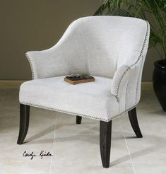 The Leisa White Armchairis will add a classic look to your Rough Luxe style. It features a soft linen and cotton slub weave in alabaster white, accented by rows of polished nickel nails and black stained, hardwood legs.