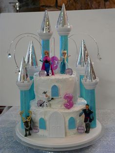 Here's the AWESOME cake I made for my Granddaughter's 3rd Birthdays.Used Wilton Castle kit. I covered towers in iridescent teal paper.Metallic silver snowflake paper for turrets. Windows teal paper, door plain. Then I added the figures and the metal crystal drops.  The figures cost the most, then the castle kit, but it was so easy.  I borrowed the cake pans from my friend Brenda who owns Elegant Catering.  Really quite simple to put together, but it looks sooooo good.