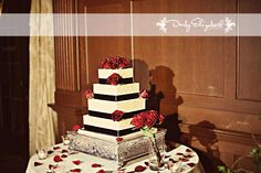 Four-tier square cake with textured white fondant, black ribbon and red roses | villasiena.cc
