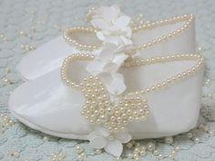 Kit de sapatinho de luxo feito em tafetá branco com bordado em pérolas e faixa de bebê combinando, para crianças de até 01 ano. Disponíveis nos tamanhos P (0 a 3 meses), M (3 a 6 meses) e G (6 a 9 meses) e GG (9 a 12 meses).