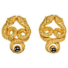 Designed as coiled gold serpents, each encircling a bezel-set deep blue cabochon sapphire. The serpent heads are accentuated with beaded gold eyes. Easy to wear, the textured 18k yellow gold earrings have a great look and good weight. The earrings are fitted with gold clip-backs. Estate Circa 1950s