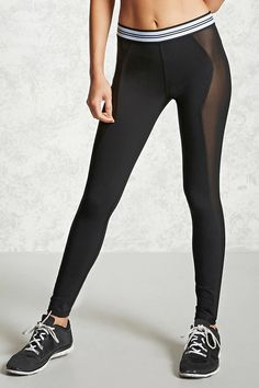 A pair of knit athletic leggings featuring sheer mesh panels and a contrast stripe waist.