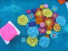 Gekleurde wol bloemen. Zelf maken? Kijk voor bollen acryl garen en flower looms eens op http://www.bijviltenzo.nl