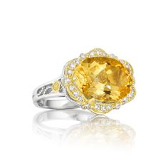 A distinctive oval shaped Citrine perks this pretty flower up! With diamond petals, warm 18k golden details, and silver accents, this ring is elegant from every angle.
