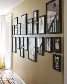 Bijzondere manier om fotolijsten te groeperen. Door de fotolijsten allemaal op de middenlijn uit te lijnen ontstaat een mooi lijnenspel.