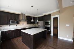The Kitchen Inside One Version of the Eleanor.  #darkcabinets #open #home #homes #kitchen #kitchenisland