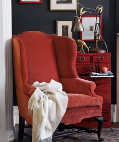 Wing chairs are a classic interior staple that will keep you warm in Winter and will never go out of style! #Wing #Chair #CozyChair #Throw #Red #Orange #Velvet #Chest #Oriental #BlueWall #Fabric #Furnishings #Interior #Design #Designer #Decor #Home