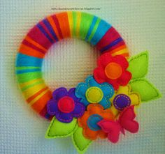 Colorful wreath.  Looks like it's yarn-wrapped then felt flowers and leaves were added.  From FELT IN LOVE
