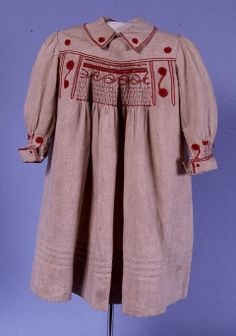 1889 long sleeved child's smock in Holland linen.  Skirt smocked into short yoke.  Embroidery on cuffs and collar and smocking at cuffs and yoke worked in red cotton.  Fastened at back with buttons and loops.