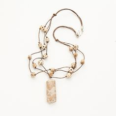 """Three-strand necklace on leather is made with carved wood and silverleaf jasper beads with a silverleaf jasper pendant. About 18-19"""" long. Sterling clasp.  myfavoritejewelrydesigners.com"""