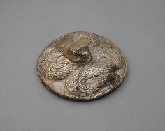 Lid (?) with a serpent  Period:Bronze Age Date:ca. late 3rd–early 2nd millennium B.C. Geography:Bactria-Margiana or eastern Iran Culture:Bactria-Margiana Archaeological Complex Medium:Silver Dimensions:Diam. 5 in. (12.8 cm) Classification:Metalwork-Ornaments