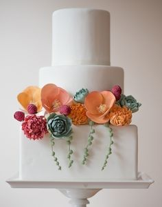 Poppies and succulents add pops of color to this smooth surfaced, tiered cake captured by Brooke Allison.