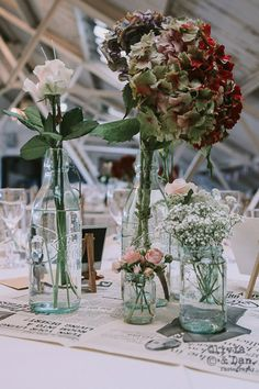 Hipster vintage wedding table decor at the super cool Dalston Heights wedding venue in East London. Gypsophila and pastel roses in jam jars on newspaper were a perfect mix of retro charm and pretty vibes.
