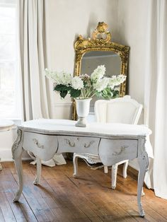 Romantic and feminine French inspired design, chair, and gilded mirror in historic home with wood floors and plaster walls. Retreat at Cool Spring in Virginia