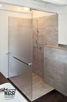 Progressiv geätzte Duschtrennwand mit Schragschnitt im Duschgefälle, Handtuchhalter und Stabilisationsstange.