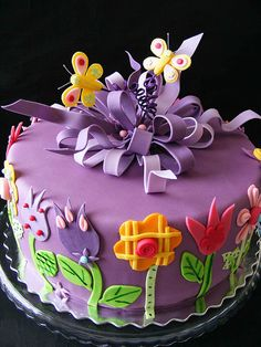 Purple cake with all color flowers. Butterflies and purple elaborate fondant bow on top. Very cute!