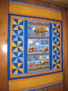 Ideas for a panel quilt and nice borders! Tonka truck construction panel to please any little boy. Blue and yellow pinwheels compliment the trucks well.