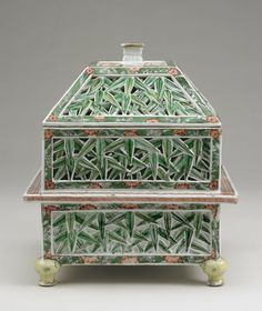 Chinese perfume-holder Pyramidal porcelain perfume casket with square cross-section. Supported on four bulbous feet, with domed cover and flattened top. Fine white porcelain with partly pierced design of bamboo leaves within conventional wave and prunus border. Kangxi period.  © The Trustees of the British Museum