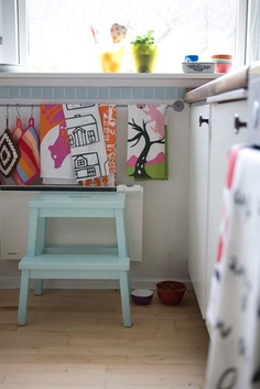 Tea towels hanging from a low wall rail and a pale blue child's stool next to white storage units