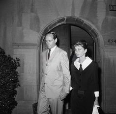 The actress Audrey Hepburn photographed with her husband Mel Ferrer (actor, dialogue coach and film director) leaving a mortuary in Hollywood, a neighborhood in the central region of Los Angeles, California (USA), after a rosary in memory of the actor Gary Cooper, on May 15, 1961.Audrey was wearing:Suit: Givenchy (of black satin, collarless jacket, with V-neckline and ¾ sleeves, single-breasted with buttons of resin in the same color, and skirt in a straight line, both pieces lined with…