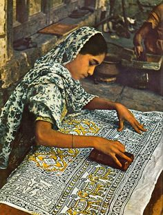 Indian Girl imprinting fabric with a block stamp