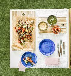 Pohľad zhora na prestretý stôl so zeleninovým ražniči na doske na krájanie a omáčkami na namáčanie v miskách.