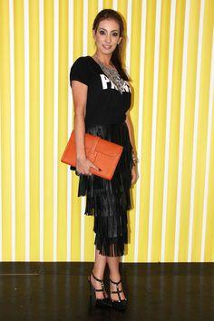 Ana Laura Penido combinou a saia de franjas de couro com camiseta e clutch laranja. Look todo da Ammis