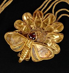 Greek Gold  and Garnet Butterfly Necklace, Late 4th-3rd Century BC  Jewelry items like this were generally used as funeral goods. In this case it's likely that the owner was a wealthy woman from the early Hellenistic period.  Butterflies are a rare representation in ancient Greek jewelry.