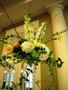 large glass vase with some flowers and branches out the top to make it look dramatic