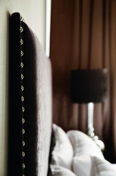 Sengegavlen har Laila fått laget, den er trukket i tekstil fra Green Apple og dekorert med nagler. Nattbordslampen er fra Anouska.