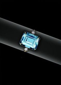 Princess Diana - The Aquamarine Ring. The Princess was first photographed wearing this ring at the preview reception for the Christie's Auction of her gowns in London, and again when she visited ydney, Australia the same summer. The ring, an emerald cut aquamarine flanked by small, solitaire diamonds and set in 24-carat yellow gold, was commissioned by the Princess from Asprey in 1997.