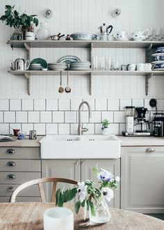 gray kitchen cabinets and shelves on wall with white farmhouse sink