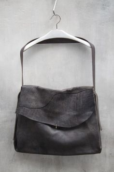 By Maurizio Amadei, a reverse calf leather large accordion bag in a midnight blue / black colour, with fold over silver hook closure, adjustable shoulder strap.