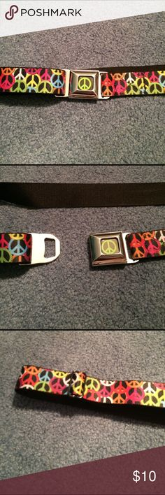 Seat belt, belt with peace signs. Like new! Black on the inside with purple, blue, yellow, pink, red, white orange and lime green peace signs. The buckle has a lime green peace sign with a black background and silver hardware. Hot Topic Accessories Belts
