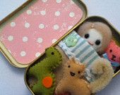 SUPER CUTE doll in a tin with kitten dinosaur and teddy bear comes with bedding too. via Etsy.