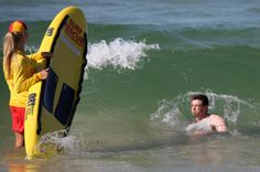 The Los Angeles Dodgers' Drew Butera, right, plunges into a wave as surf lifesaver Sophie Thomson holds a rescue board at Bondi Beach in Sydney, Wednesday, March 19, 2014. The Major League Baseball season-opening two-game series between the Los Angeles Dodgers and Arizona Diamondbacks in Sydney will be played this weekend. (AP Photo/Rick Rycroft)