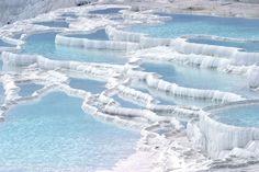 La cascata bianca di Pamukkale, Turchia. Nel corso di milioni di anni, le sorgenti calde di Pamukkale hanno trasformato il paesaggio. Anche se può sembrare che queste terrazze siano fatte di ghiaccio e neve, la Turchia ha un clima caldo tutto l'anno. Il suolo è coperto da calcare bianco.