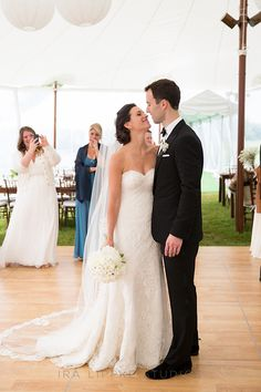 The bride and groom at their tented wedding reception | @iralippke | Brides.com