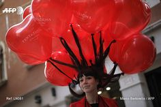 A woman's hair is held up by floating balloons as revellers dressed in masks and period costume take part at the Venice Carnival on February 12, 2017 in Venice. Marco BERTORELLO / AFP