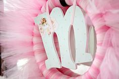 Love this cute wreath made out of  tulle and a wooden letter! Perfect for a birthday child. This was made for a ballerina birthday party. Found via Kara's Party Ideas.