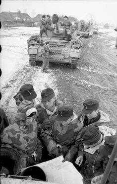 A column of Panzer IV tanks, with soldiers at briefing behind a lead tank, using it as cover.