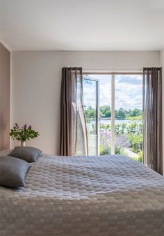 Pretty and simple bedroom in delicate tones and a fantastic view over the lake.