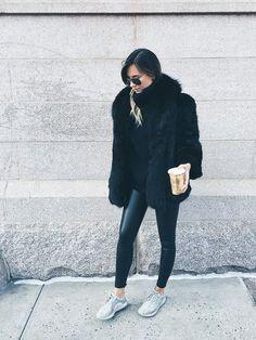 Danielle Bernstein of We Wore What wears a black sweater, fur coat, leggings, Yeezy Boost sneakers, and aviator sunglasses
