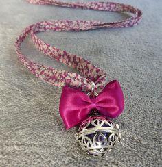 Bola de grossesse avec motif de feuilles indiennes et ohm, contenant une bille violette, avec un noeud fuschia, en sautoir : Collier par bola-de-grossesse
