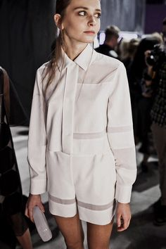 classic silhouette of button up and short is made interesting by a composition using line and shape both in a very organized and geometric was to make it feel formal and positive and neg. space (opaque panels), unified by white colour