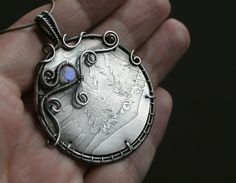 My first etched pendant. It's made of etched (and silver plated) nickel silver (or german silver) disc wrapped with silver plated wire and a blue flashy rainbow moonstone coin bead. It's already so...