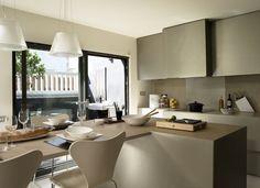 Cocina con acceso a la terraza compuesta por isla y mesa alargada. Muebles de cocina en tonos grises y vitrocerámica y sillas de color blanco con estructura...