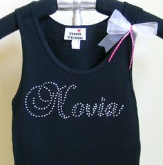This Novia tank T-shirt has a beautiful script in crystal rhinestones.  A matching detachable white organdy bow with a bit of pink and white dots completes the look.