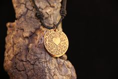Two copper discs hang one in front of the other, the front is etched with a heart and vines, the back is hand stamped with Heart and Soul and