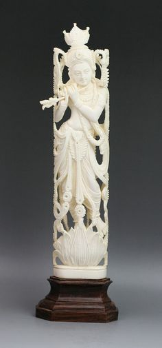 """Antique Indian Ivory Carved Goddess Lakshmi: finely carved and fully reticulated throughout: standing on a lotus pedestal base playing a flute: with wood stand: Late 19th century   Dimensions: Ivory: 8""""; Overall: 9-1/2"""""""